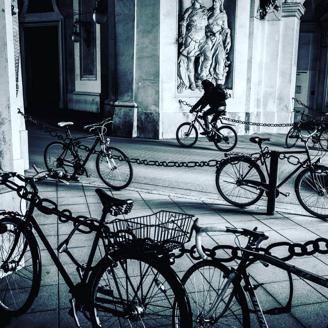 A man rides his bike through an alley in Hofburg Palace in Vienna, Austria